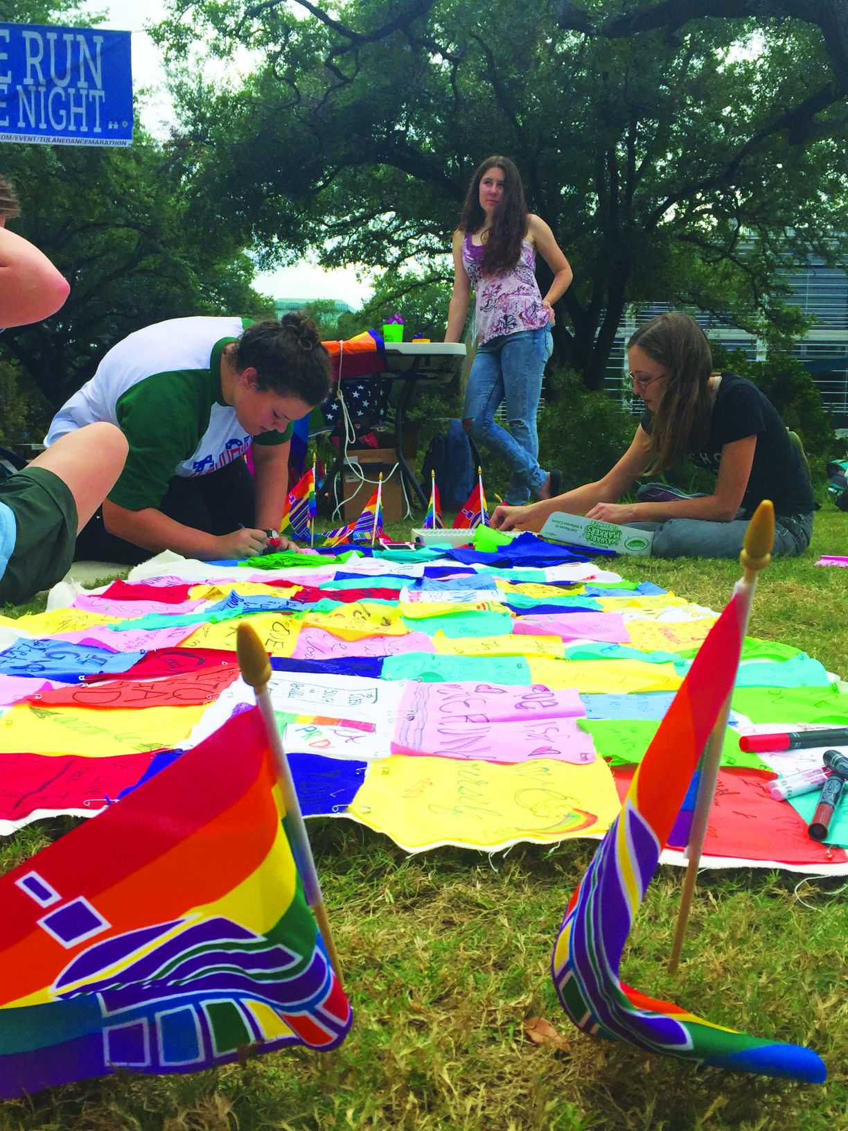 Students gather Monday to celebrate the kickoff of Pride Month on the Lavin-Bernick Center quad. Students came together to write messages of encouragement on a banner for the festivities.