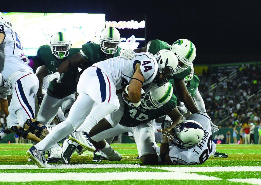 The+Green+Wave+team+tackles+UConn+redshirt+sophomore+running+back+Max+DeLorenzo+in+a+7-3+Tulane+home+loss+on+Saturday%2C+November+7.