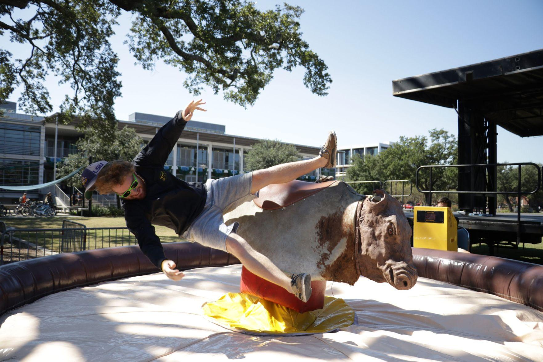 As part of the day's Homecoming festivities, Homecoming King nominee Bobby Martin rides a mechanical bull Oct. 27 on the Lavin-Bernick Center Quadrangle. Other festivities for the afternoon included making emoji pillows and creating personalized signs.