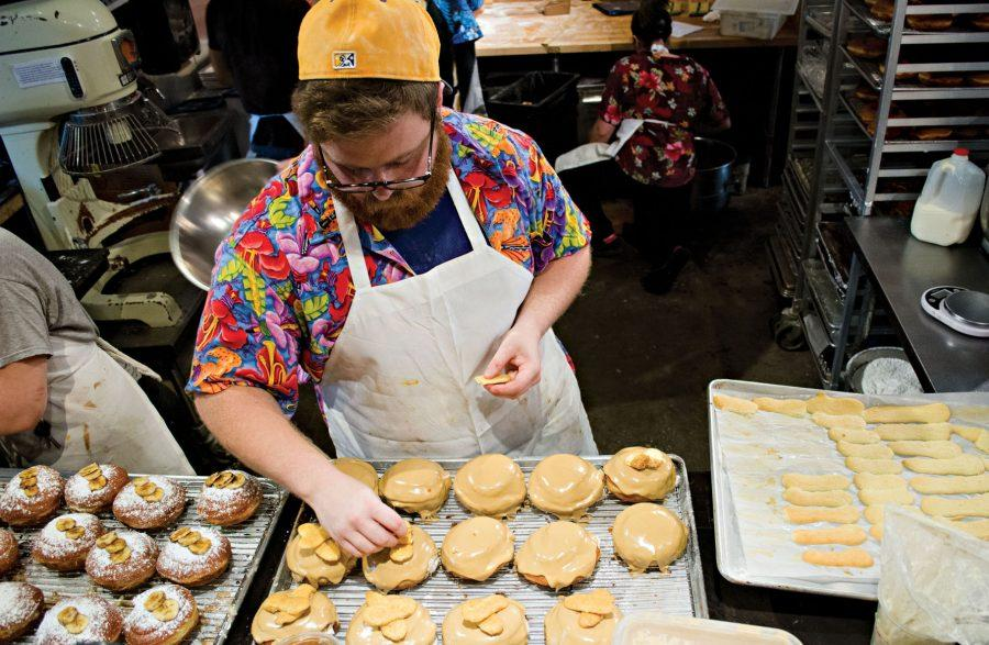 Tulane senior Jonah Resnick, an aspiring baker, ices freshly made donuts during his shift at District Donuts on Magazine Street. Resnick has been working at District Donuts for around five months, and hopes to continue baking and to one day own his own bakery.
