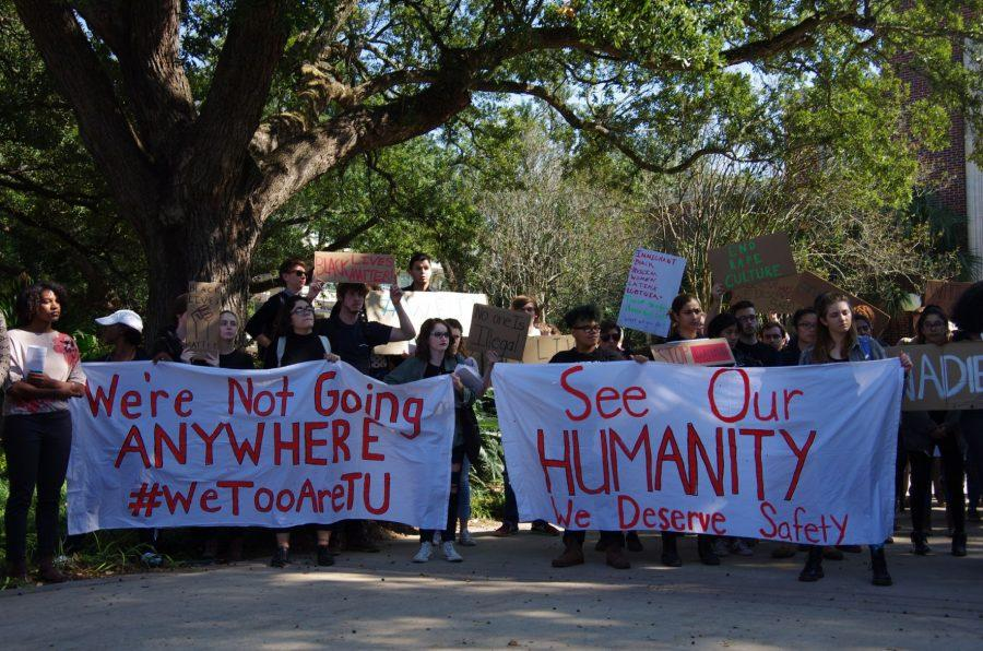 Demonstrators holding signs and banners gather outside McAlister Auditorium to listen to students share their personal experiences with racism and marginalization at Tulane.