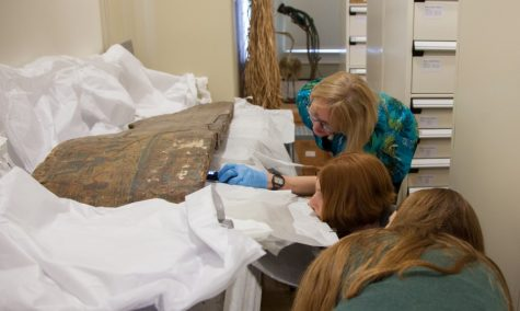 Mimi Leveque (back), Melinda Nelson-Hurst (middle) and Caroline Parris (front) examine part of the coffin of Amenemope.