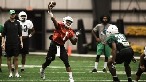 Tulane's starting quarterback, Jonathan Banks, goes back to pass at a summer practice session.