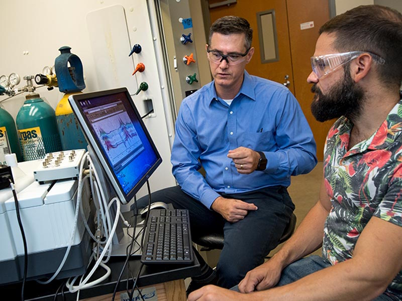 Professor Daniel Shantz (left) and graduate student Ross Ransom (right) analyze data from their research of zeolite SSZ-39 in an effort to reduce harmful chemicals in auto emissions.