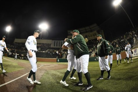 Head coach Travis Jewett celebrates with his team in a game against the Purdue Boilermakers. This is Jewett's second season as head coach of the Green Wave.