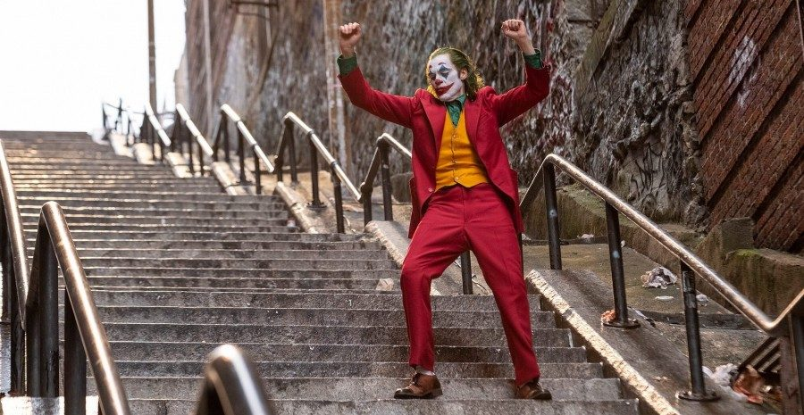 "oaquin Phoenix prances down a set of stairs in the film ""Joker."" Courtesy of Niko Tavernise/Warner Bros"