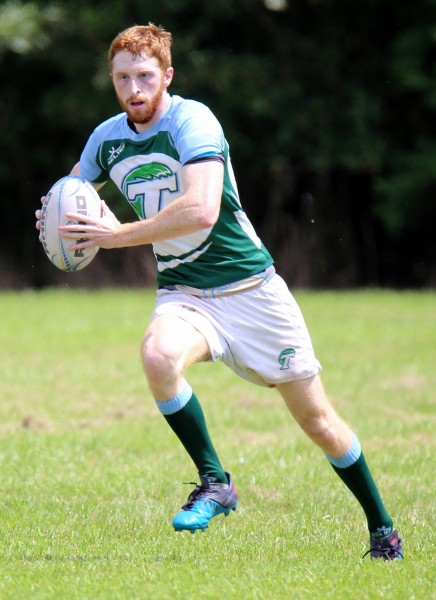 Rugby player runs with the ball.
