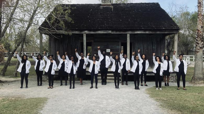 The 15 White Coats stand in front of Whitney Plantation as a symbol of their heritage and as inspiration for future doctors everywhere.