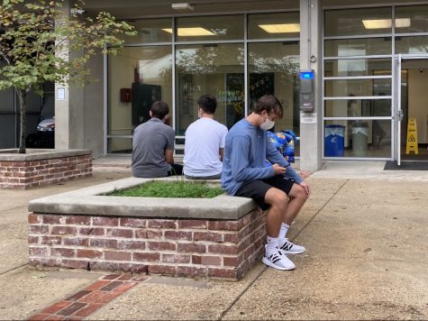 Students sit outside Monroe residence hall.