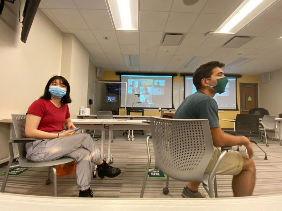 Students wear masks for in-person class as the board projects the tech-enhanced Zoom class with distance-learning students.