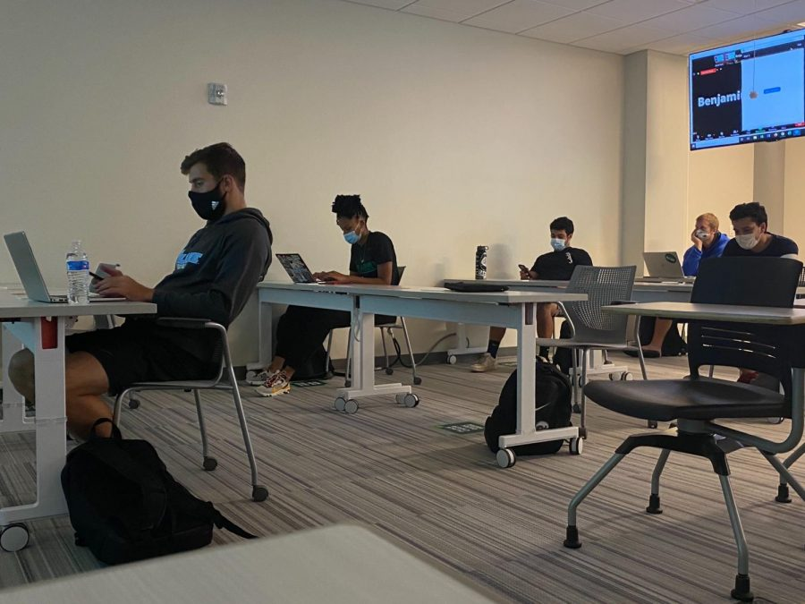 Students wear masks and  use their laptops in the socially-distanced classroom.