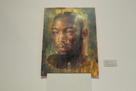 photo of work of mans face with vial in front of it in ogden exhibit