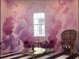 pink cloud art wall with a window in the center, black and white striped floor, table with two chairs, wicker chair in corner