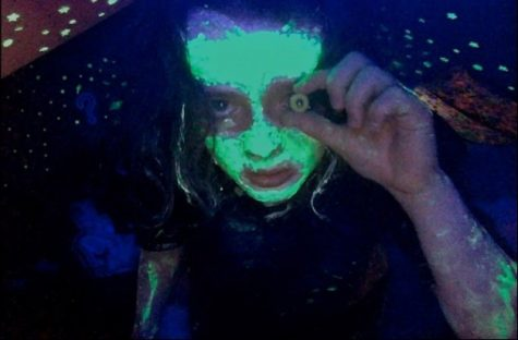 person with neon green on their face and arms holding a cheerio in front of their eye