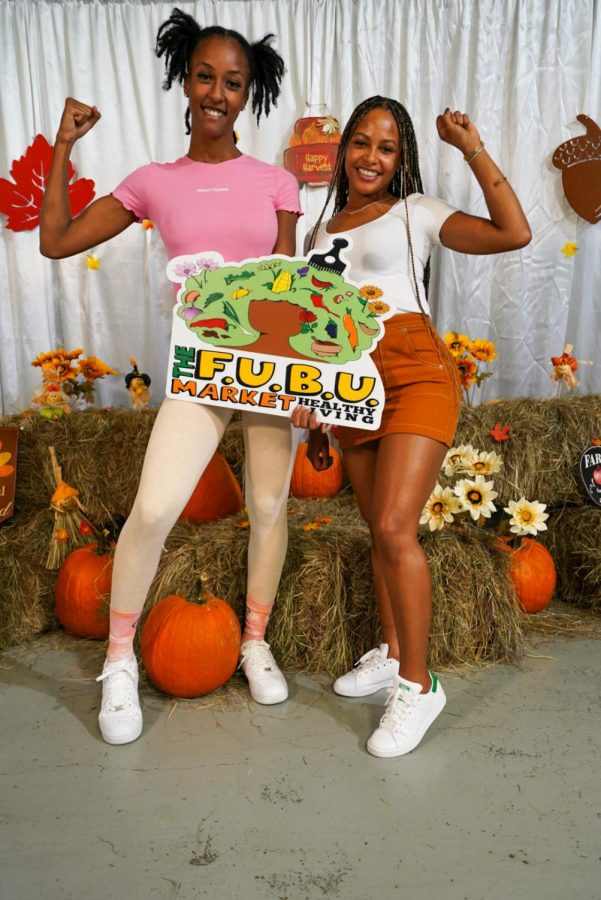 """two women holding a sign that reads """"the fubu market"""""""