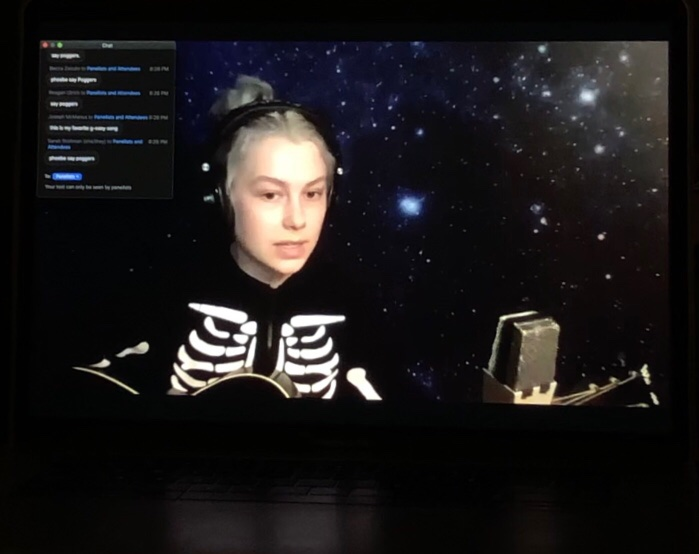 phoebe bridgers holds a guitar while singing in a skeleton sweatshirt in front of a galaxy background