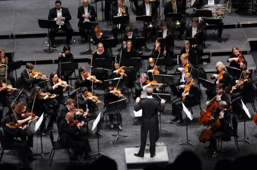 orchestra is playing on a stage with conductor up front