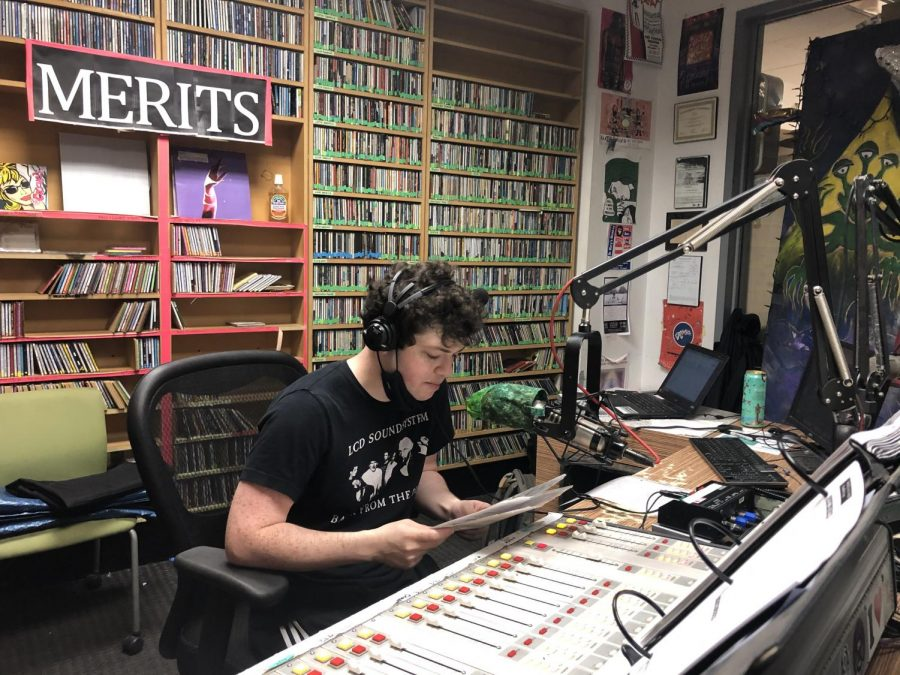 student dj sits in front of microphone to host a section of the marathon in the wtul office