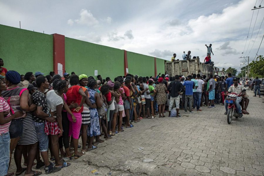 People wait for food to be distributed in Les Cayes, Haiti.