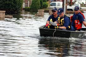 men in a boat in floodwaters